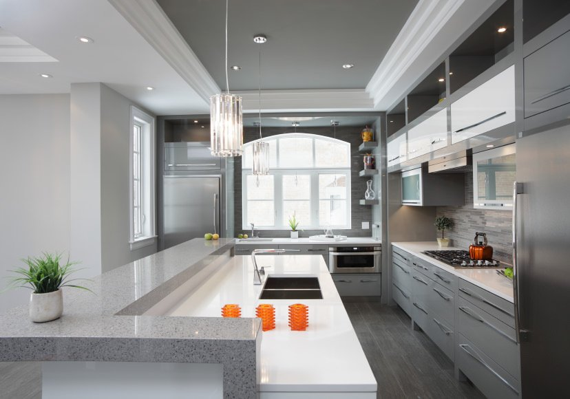 A kitchen featuring a nice island with a breakfast bar lighted by gorgeous ceiling lights set on the tray ceiling. The room also features gray hardwood flooring and gray cabinetry.
