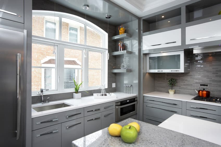 The gray walls, kitchen counters and cabinetry make this industrial kitchen look stylish. The smooth white countertops look perfect together with the gray shade surrounding the space.