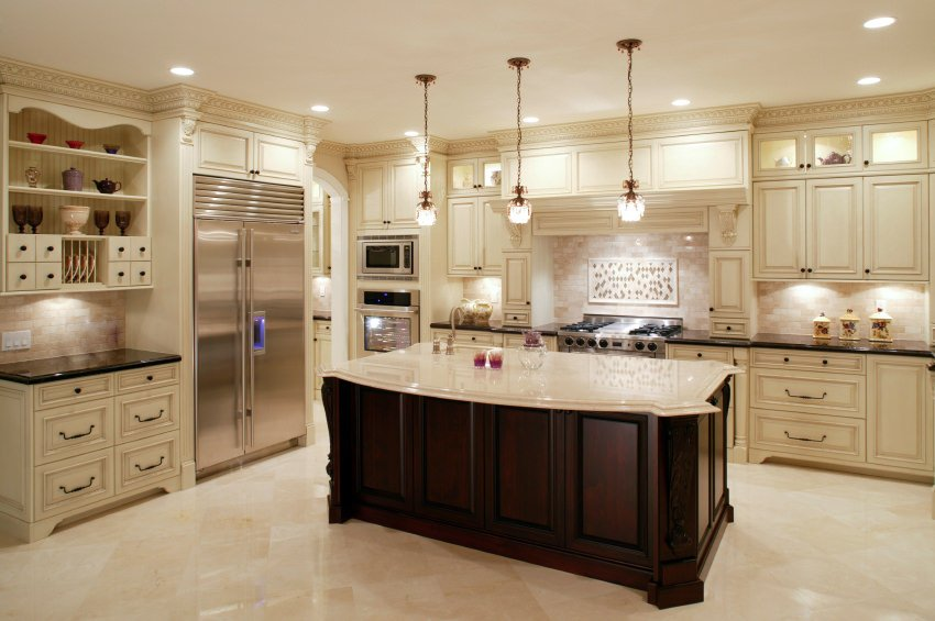 A classy kitchen set featuring tiles floors matching the tiles backsplash. It also features a large center island with a smooth white countertop.
