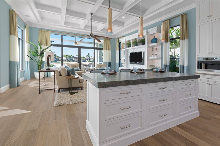 A great room featuring a cozy living space and a kitchen with thick stylish countertops on both center island and kitchen counters. The room features hardwood floors, blue walls and a coffered ceiling.