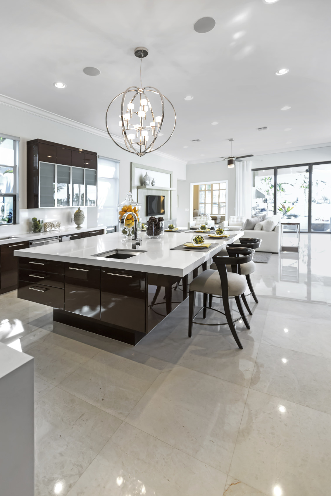 A modish kitchen set featuring white walls and chocolate brown details are so beautiful to look at, but the main attraction here is the gigantic center island featuring a captivating smooth white countertop lighted by a beautiful ceiling light.