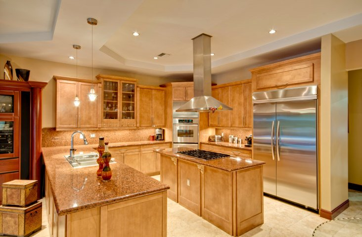 This bright kitchen features walnut finished cabinetry, backsplash and countertops. There's a narrow center island as well.