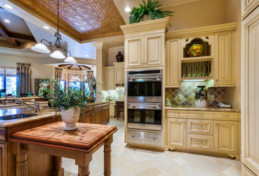 This is Mediterranean-style kitchen with a beige tray ceiling that houses ceiling tiles on the middle tray. These are textured and has a brown tone that complements the beige peninsula while matching the kitchen island.
