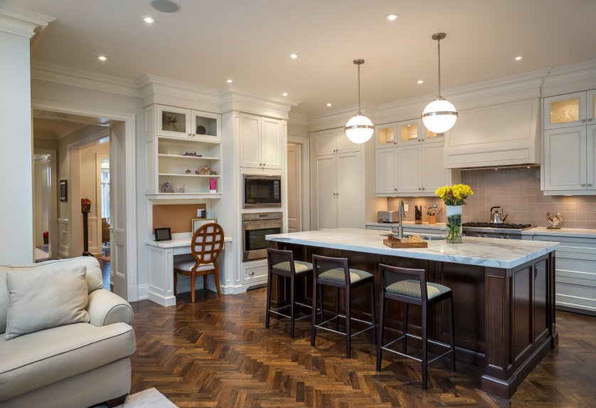 Cozy kitchen with white cabinetry and built-in desk paired with a round back chair. It includes a dark wood kitchen island with sink and matching bar stools over herringbone wood flooring.