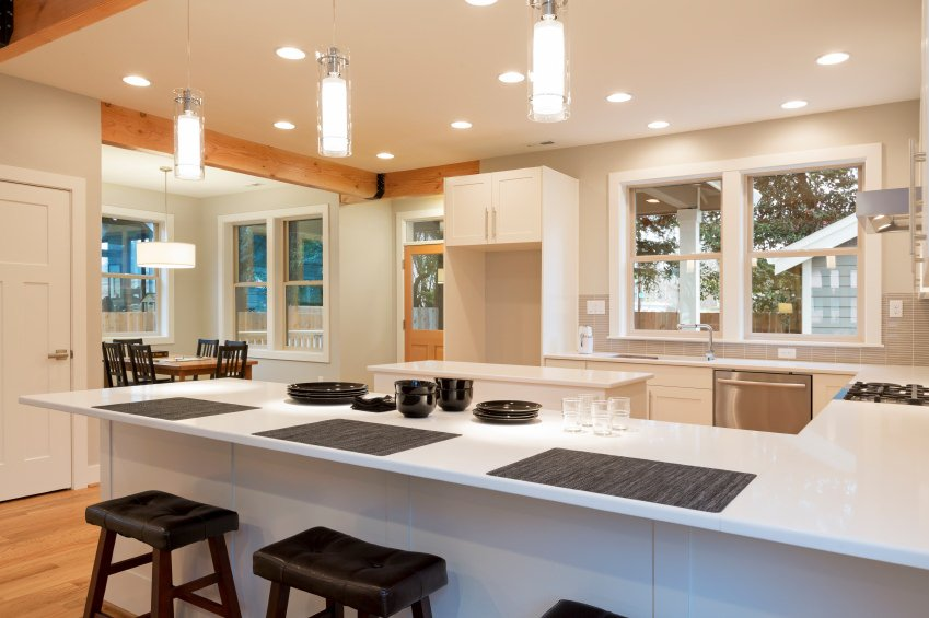 This kitchen features smooth white counters spreading across the kitchen lighted by recessed and pendant lights.