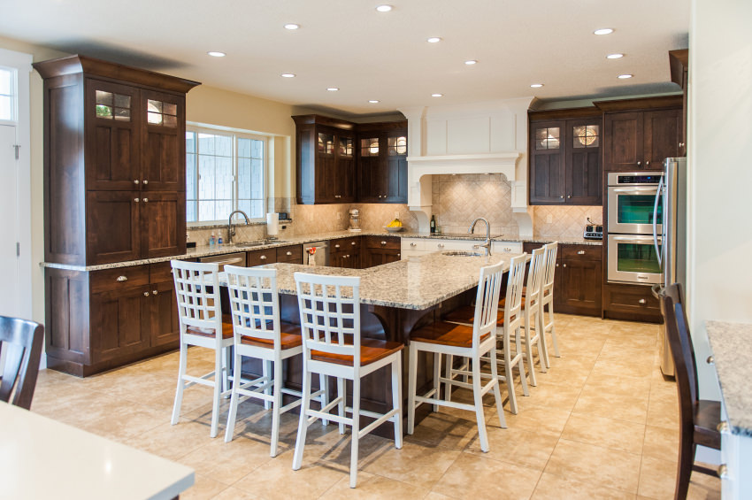 Gorgeous kitchen showcases wood stained cabinetry contrasted with a white vent hood fixed to the ceramic tile backsplash. It includes an L-shaped kitchen island lined with white counter chairs.