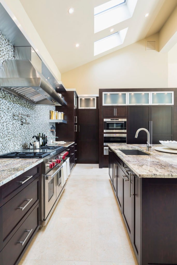 A close up look at this kitchen's counters and center island with classy countertops and gorgeous shed ceiling with skylights.
