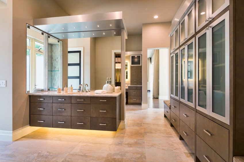 This large modern closet features a tiles flooring, classy cabinets and beautifully set recessed ceiling lights.
