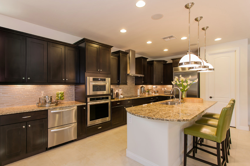 Large kitchen setup featuring dark brown cabinetry and kitchen counters with granite countertops. There's a large center island as well, providing space for a breakfast bar lighted by classy pendant lights.