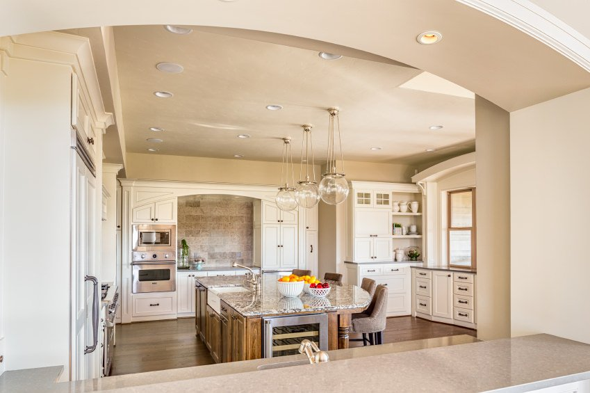 Is this a Mediterranean style white kitchen? It's close. The arches and earthen backsplash along with the hardware and rustic wood island makes me think falls into the Mediterranean style. Regardless, it's a beauty.