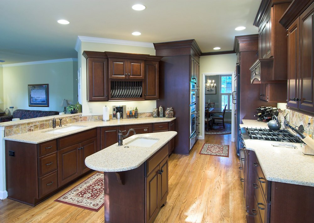 This kitchen features a small center island and a peninsula, both boasting marble countertops and lighted by recessed ceiling lights.