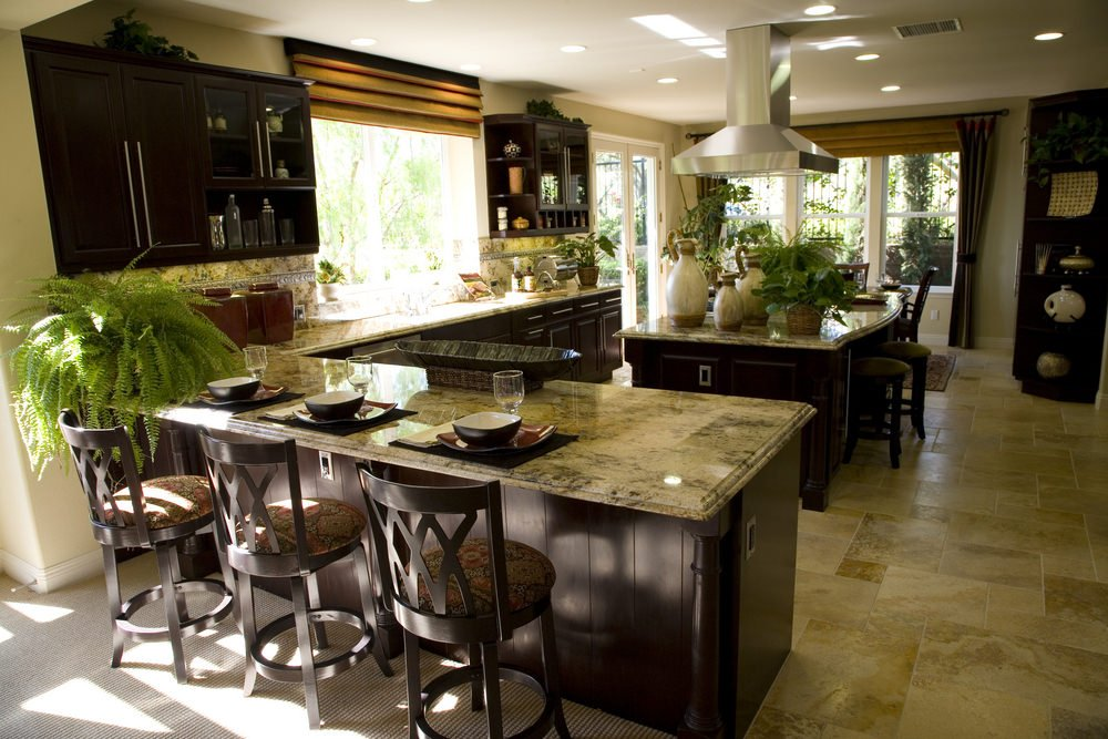 This kitchen boasts spresso details nad tiles flooring. The marble counters and backsplash spread across the whole kitchen.