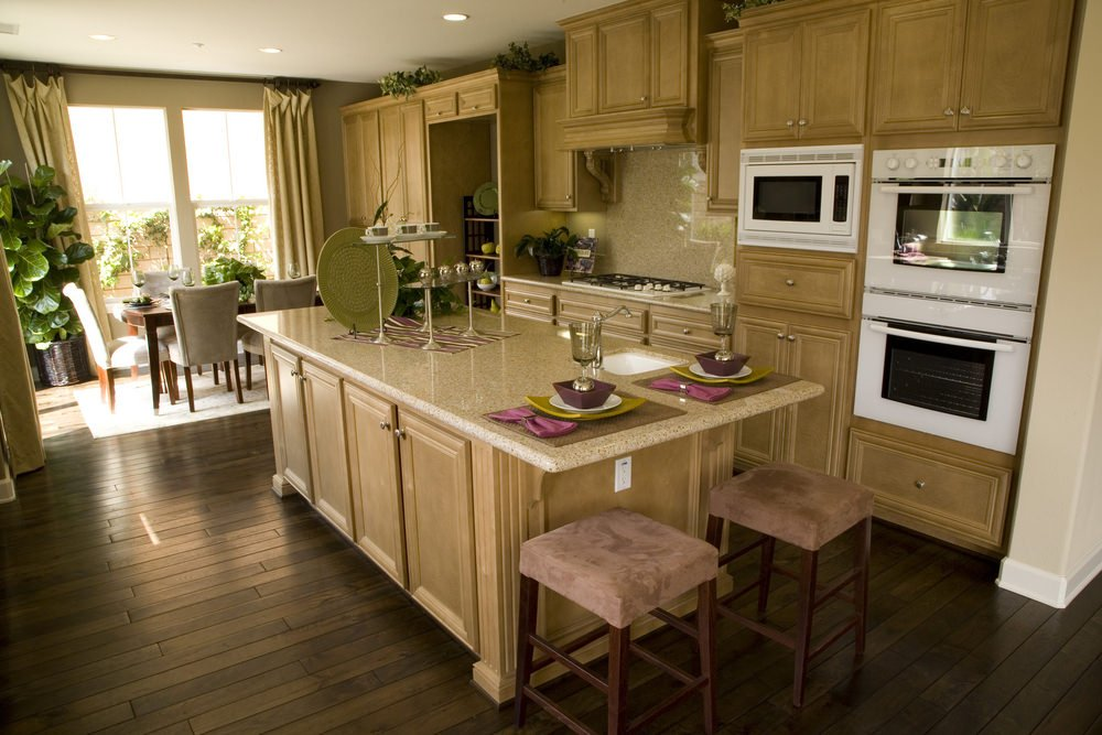 Small kitchen with walnut finished cabinetry and kitchen counters along with the center island set on the hardwood flooring.