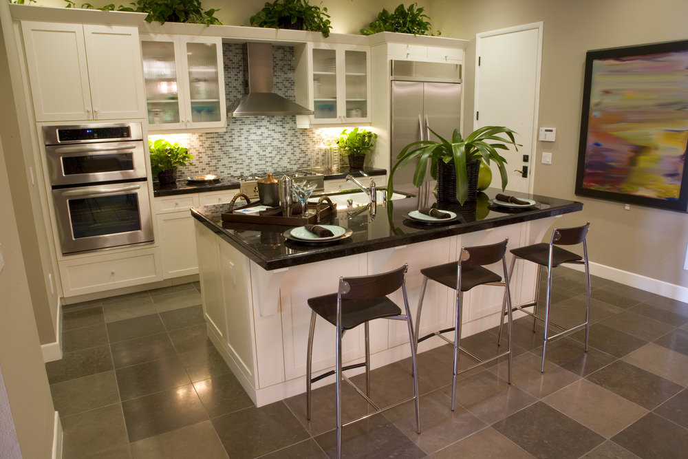Modern kitchen features a black granite top breakfast island and white cabinetry accented with mosaic tile backsplash and indoor plants that create a refreshing ambiance to the room.