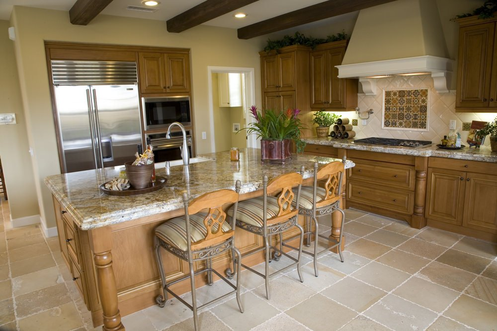 Taupe kitchen with tiled flooring and white ceiling lined with dark wood beams. It includes natural wood cabinetry and diamond patterned backsplash topped with decorative tiles underneath the vent hood.