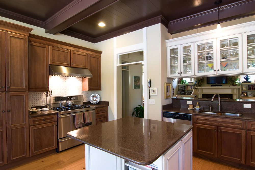This kitchen features a small center island set on the hardwood flooring. The recessed lights look perfect for this kitchen, which also features a ceiling with beams.