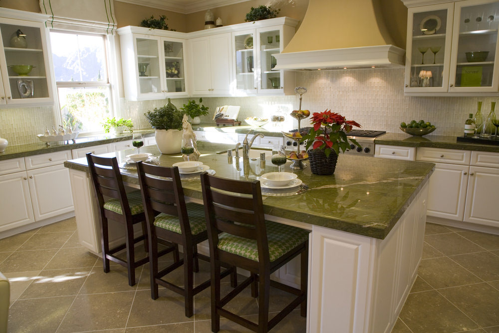 Charming kitchen boasts white cabinetry and backsplash tiles fixed against the yellow walls. It has a breakfast island with marble counter and white sink lined with wooden chairs that are fitted with green patterned cushions.