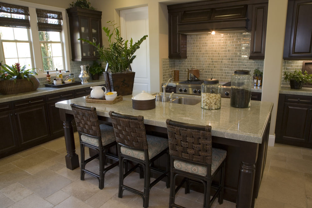 Tropical kitchen features subway tile backsplash and a dark wood kitchen island topped with marble counter and lined with woven chairs fitted with floral cushions.
