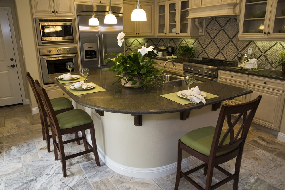 A small kitchen with white cabinetry and mosaic backsplash tiles along with a curved breakfast island fitted with a dual sink and paired with green counter chairs.