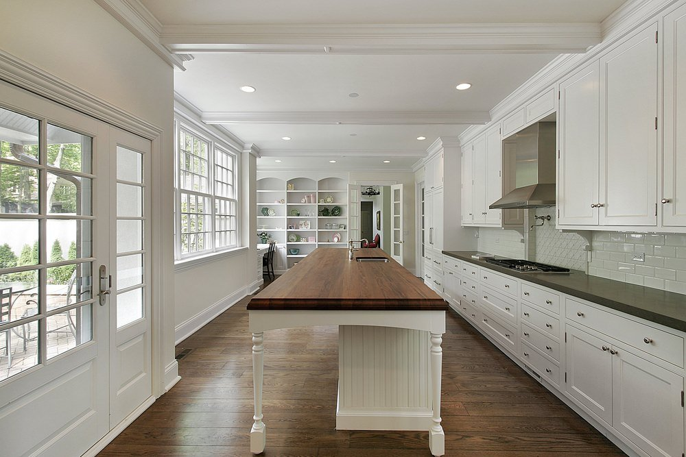 A white kitchen island with dark wood surface stands in the middle of a single-wall white kitchen that faces a wall of French doors and windows.