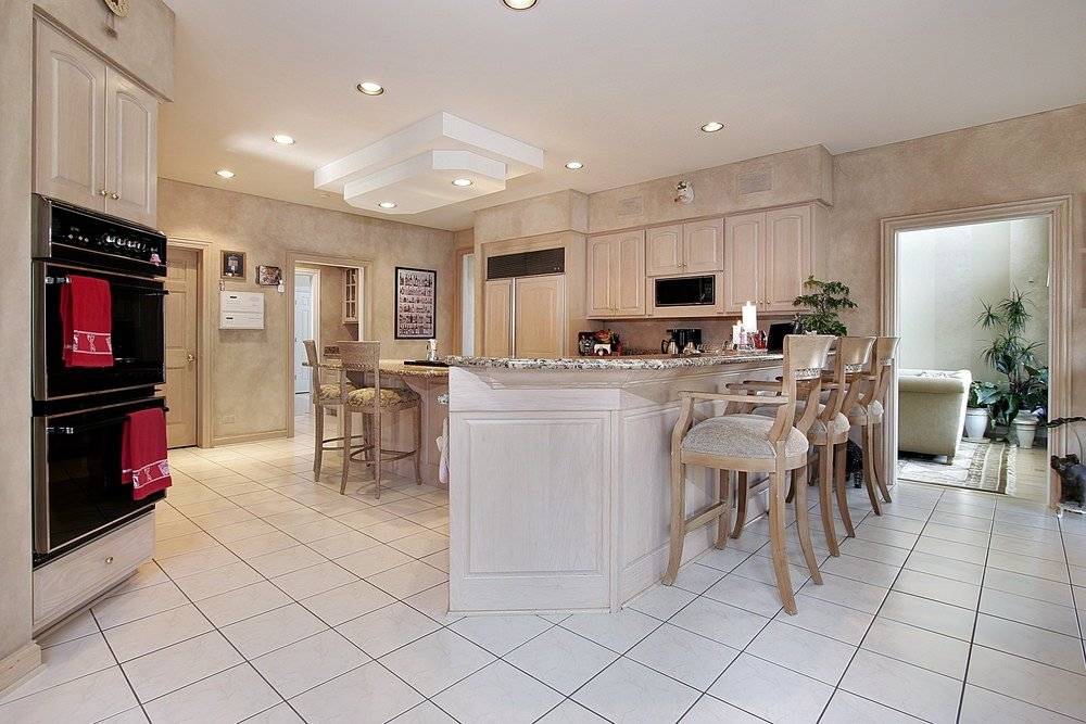 Gorgeous kitchen with marble tiled flooring and drop ceiling suspended over the breakfast island that matches with the light wood peninsula lined with wooden chairs.