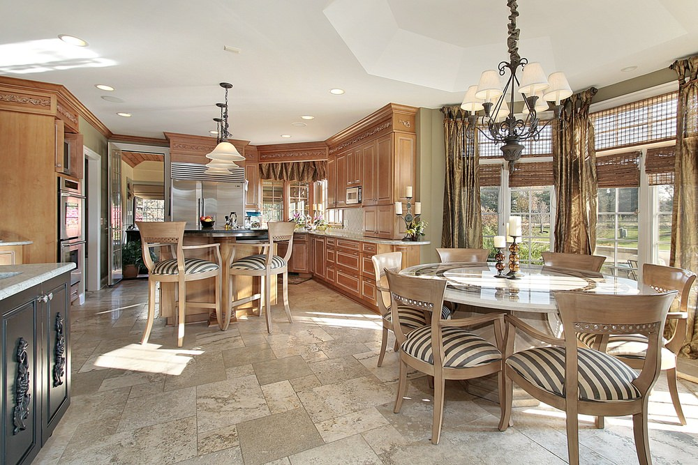 This kitchen offers limestone flooring and glass windows covered with wicker roman shades and draperies. It includes a wooden breakfast island and round dining table paired with striped cushioned chairs.