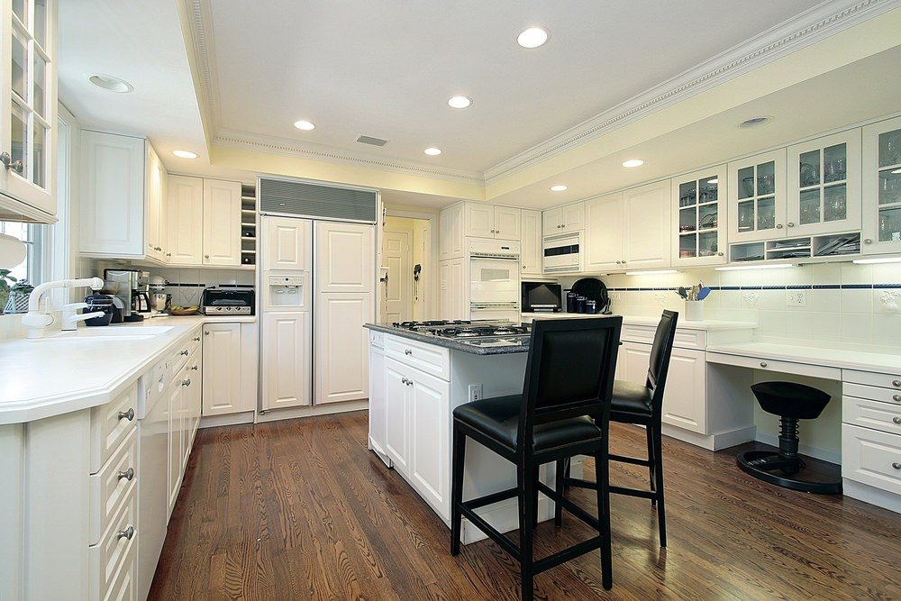 Large kitchen with white walls, cabinetry, kitchen counters and center island set on the hardwood flooring.
