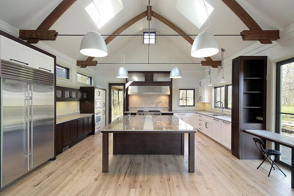 Large kitchen featuring a massive center island set on the hardwood flooring. The ceiling lights set on the high ceiling look magnificent as well.