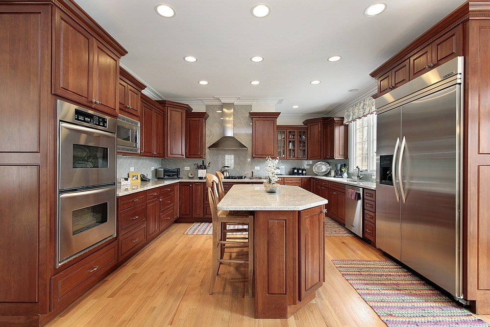Cozy kitchen features a wooden island bar over hardwood flooring topped by lovely kitchen runners. It is surrounded with wood cabinetry and stainless steel appliances along with vent hood fixed to the glossy backsplash tiles.