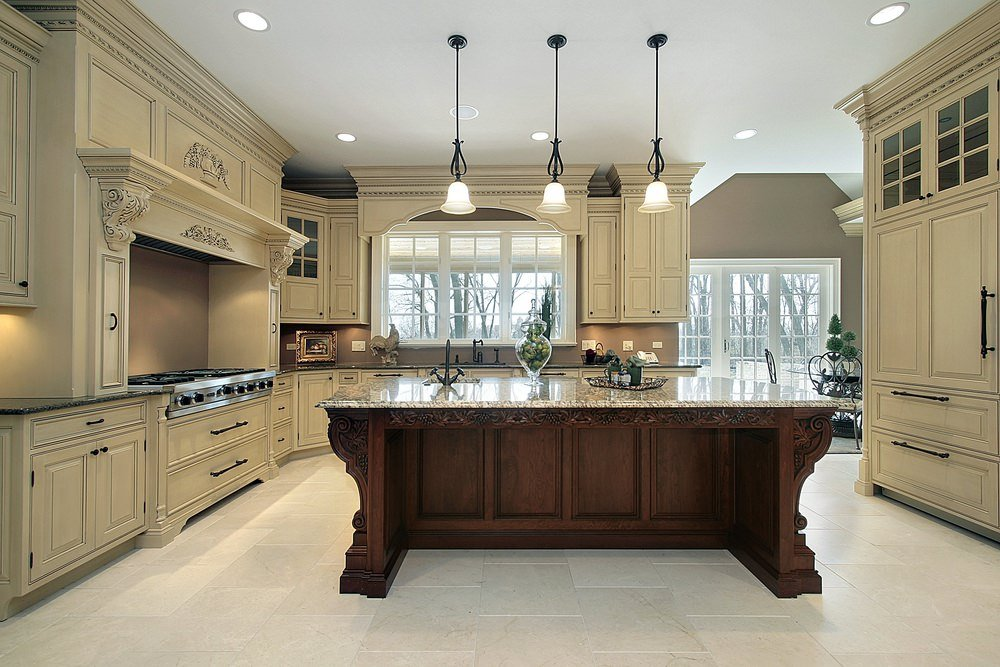 An empty kitchen offering a large and classy center island set on the white tiles floors.