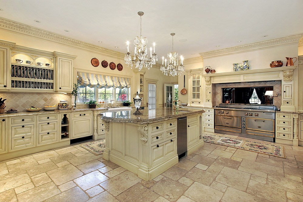 Large Mediterranean kitchen with tiles flooring and an elegant style of cabinetry and center island. The two classy chandeliers flood the kitchen with brightness.