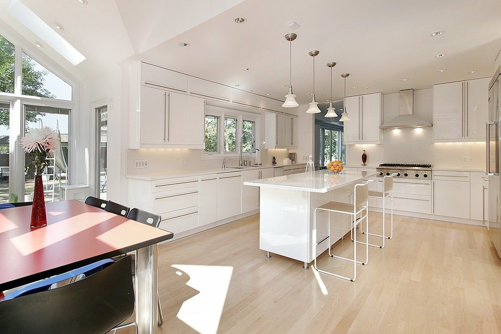 Sleek kitchen boasts white cabinetry and island bar illuminated by pendant lights. It has a red dining table and black chairs over light hardwood flooring.
