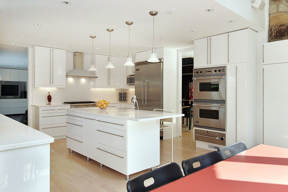 A Scandinavian-Style kitchen with white walls, cabinetry, counters and center island with smooth white countertop. The room is lighted by recessed and pendant lights.