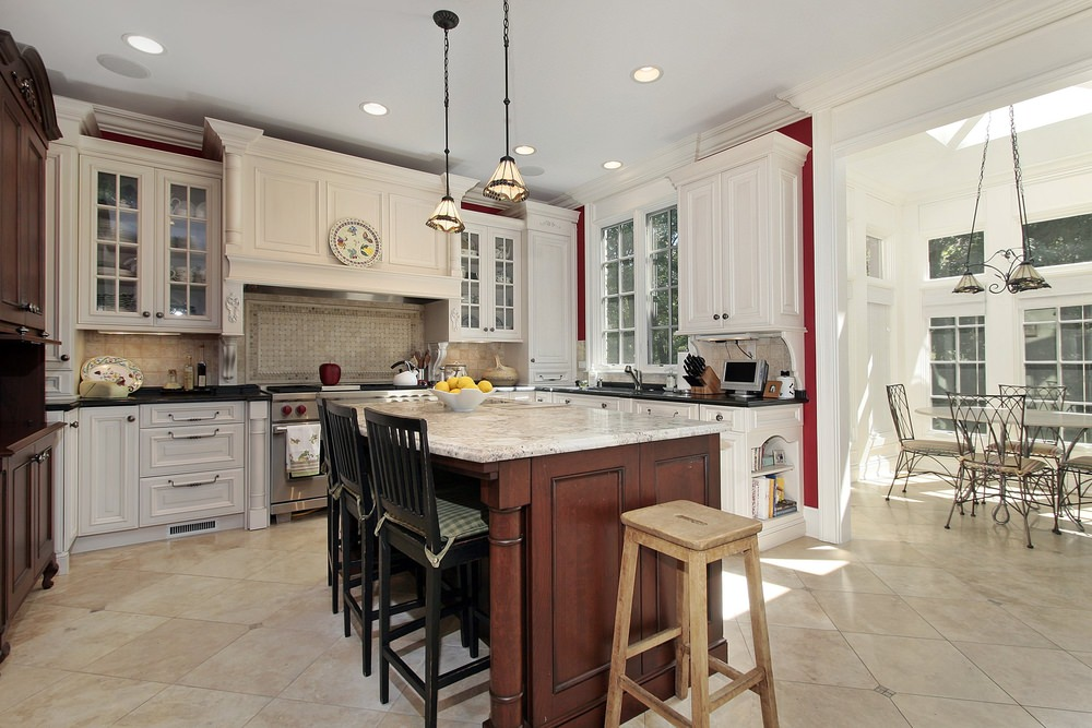 Classic kitchen with a wooden breakfast island topped with white marble counter and accompanied by a wooden stool and black chairs with green checkered cushions.