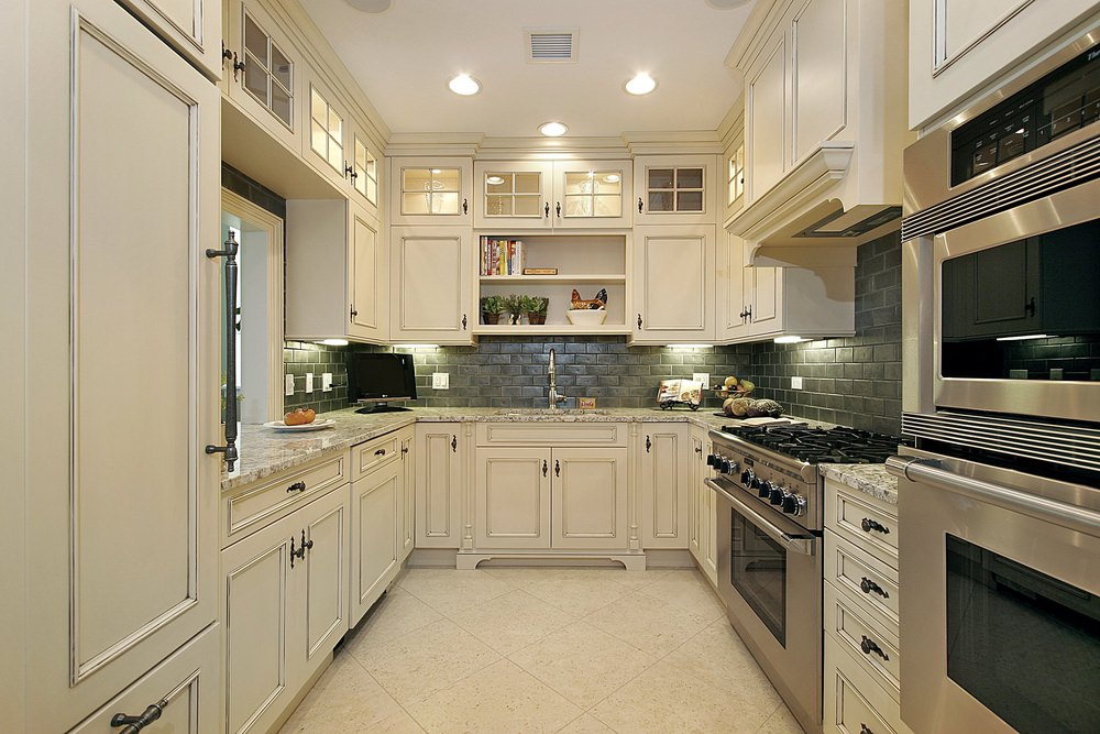 U-shaped kitchen with white counters and cabinetry along with white marble countertops and white tiles flooring.