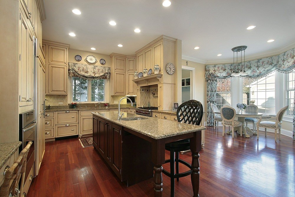Traditional kitchen featuring reddish hardwood floors and beige cabinetry and kitchen counters, along with a dining nook on the side near the windows.