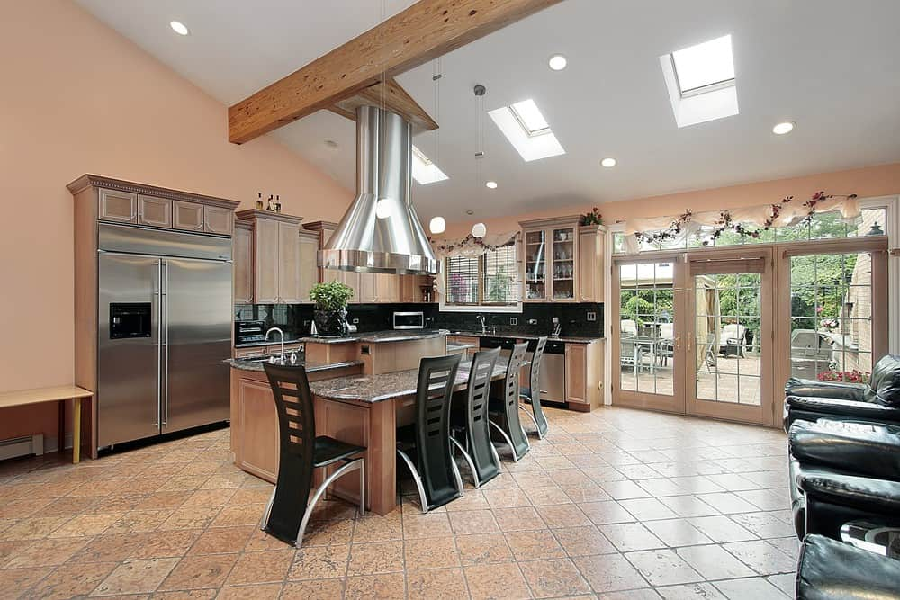 A stainless steel range hood stands over the three-tier island bar in this kitchen with a serving counter lined with stylish black chairs. It has glass windows and a vaulted ceiling with exposed wood beam and skylights.