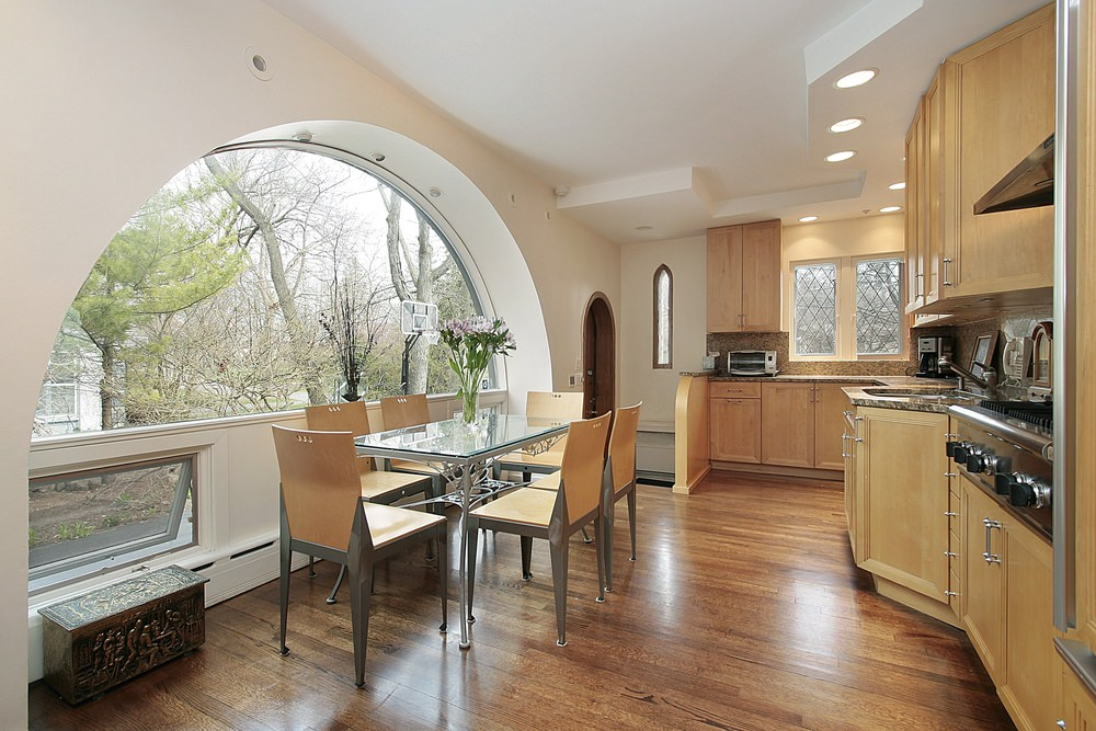 Fresh kitchen with light wood cabinetry and stylish dining set by the semi-circular glass window fitted with recessed lighting.