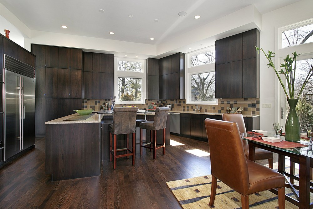 Asian style kitchen with dark hardwood flooring that compliments with the cabinetry. It has beige tile backsplash and white framed glass windows allowing natural light in.