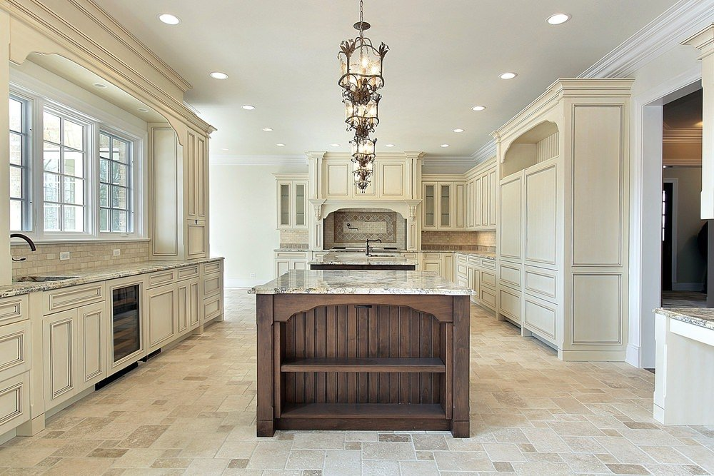 An empty kitchen featuring tiles floors, wooden center island with marble countertops and a set of lined up pendant lights.
