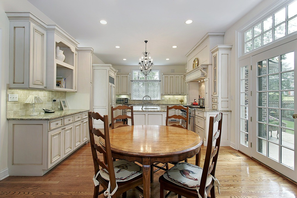 A dine-in kitchen with white cabinetry and checkered backsplash tiles along with wooden dining set next to the breakfast island illuminated by a vintage chandelier.