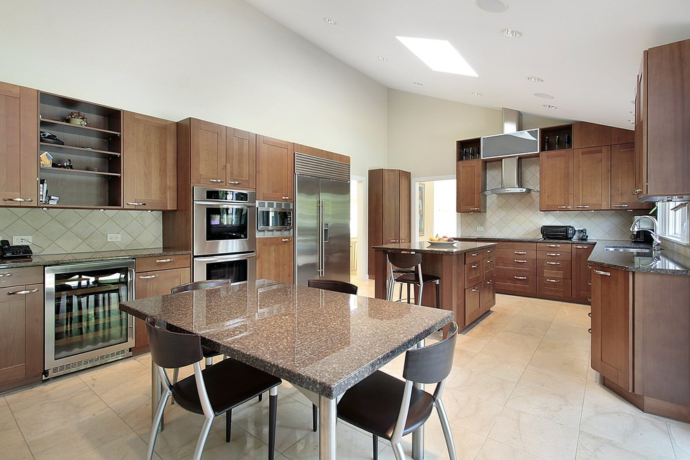 Large kitchen featuring brown cabinetry and kitchen counters with black granite countertops. The floors look classy together with the shed ceiling.