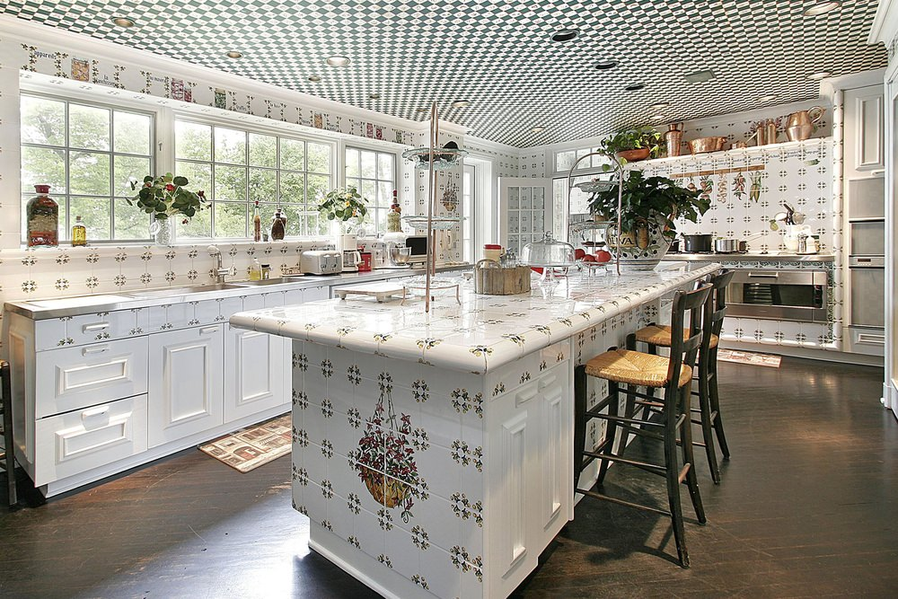Fabulous kitchen showcases distressed hardwood flooring and an eye-catching ceiling fitted with recessed lights. It has a kitchen island clad in decorative tiles that match with backsplash tiles.