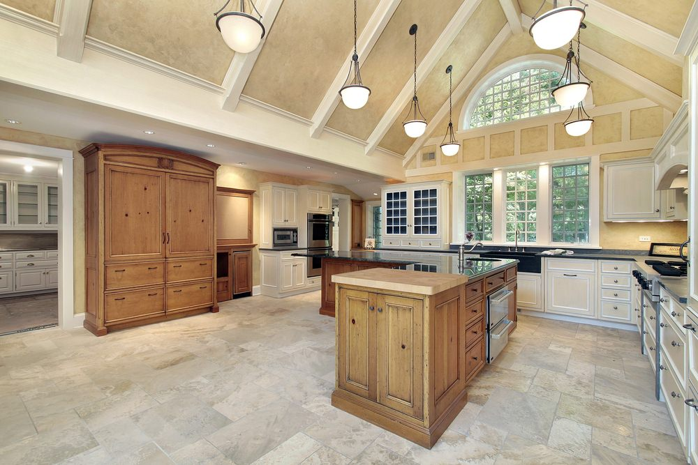 Large kitchen with a beautiful vaulted ceiling with beams, lighted by charming pendant lights. The kitchen also features tiles flooring and black marble countertops.