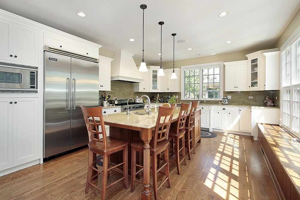Bright kitchen boasts white cabinetry with black knobs and a wooden breakfast island illuminated by pendant lights.