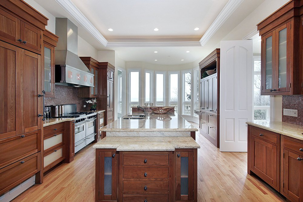 This large kitchen features a tray ceiling with recessed ceiling lights and hardwood flooring matching the cabinetry and kitchen counters. The marble countertops look perfect together with the white walls.