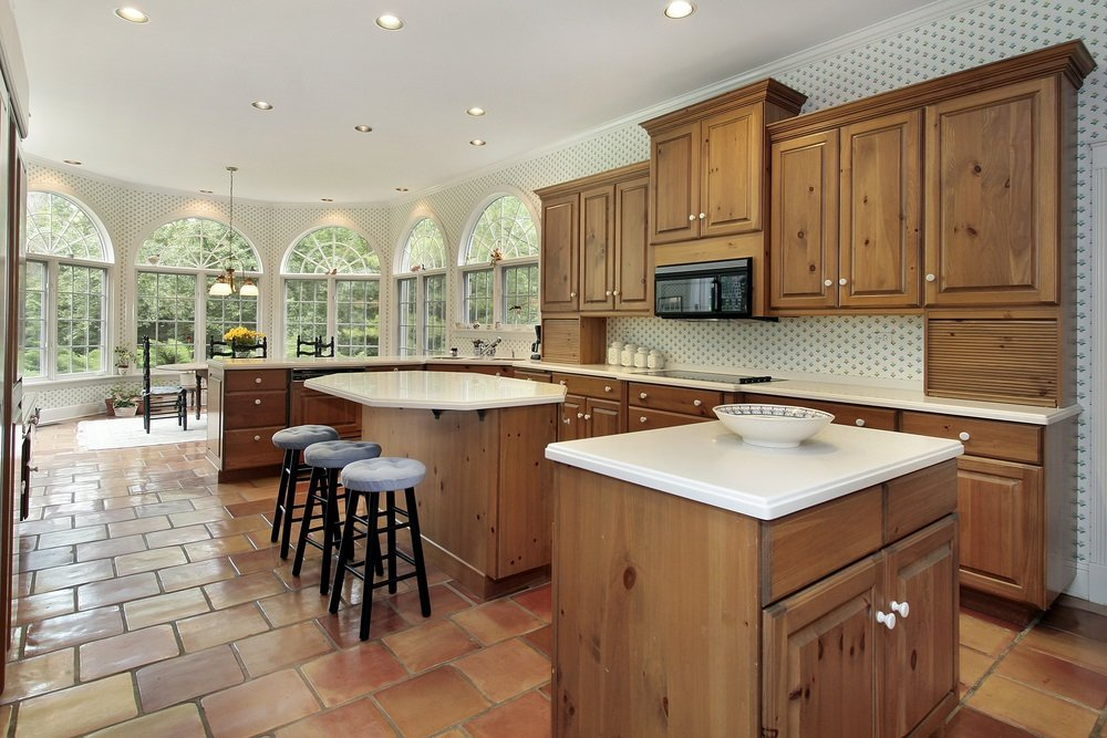 Airy kitchen with terracotta brick flooring and arched windows overlooking the outdoor greenery. It includes double kitchen islands that match with the wooden cabinetry.