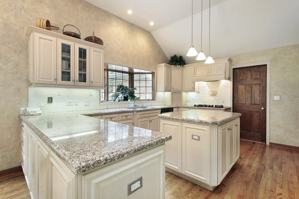 This kitchen features a hardwood flooring and white ceiling with pendant and recessed lights. The center island and the peninsula both features marble countertops.