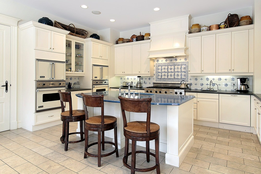 Charming kitchen showcases white cabinetry topped with lovely vases and accented with decorative backsplash tiles that complement with the blue countertop fitted on the white kitchen island.