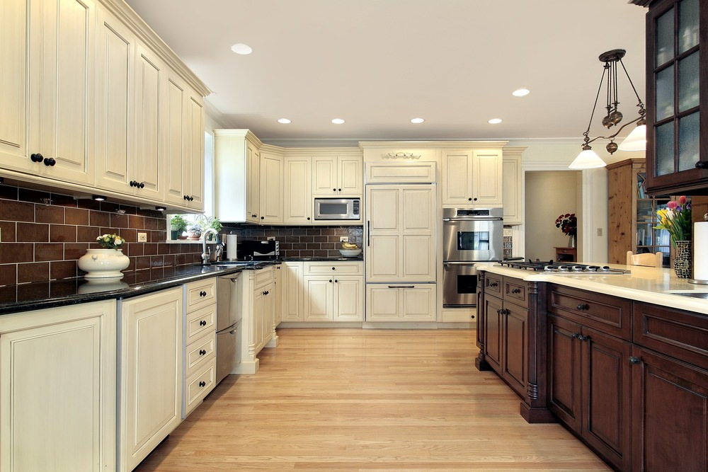 This kitchen boasts brown tiles backsplash, white cabinetry and kitchen counters and hardwood floors.